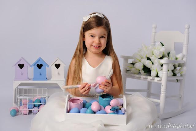 Mała dziewczynka pozuje usmiechnięta do zdjęcia w studio świątecznym