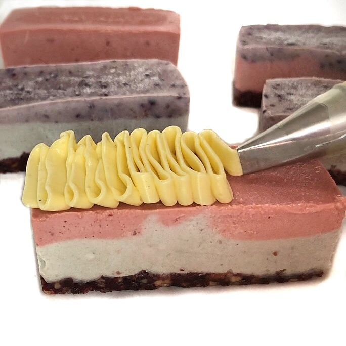 Piping frosting on a raw cheesecake