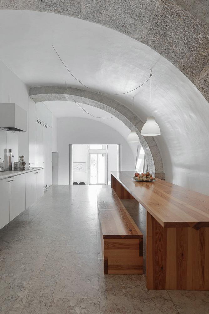 Cocina blanca minimalista con mesa y banco de madera
