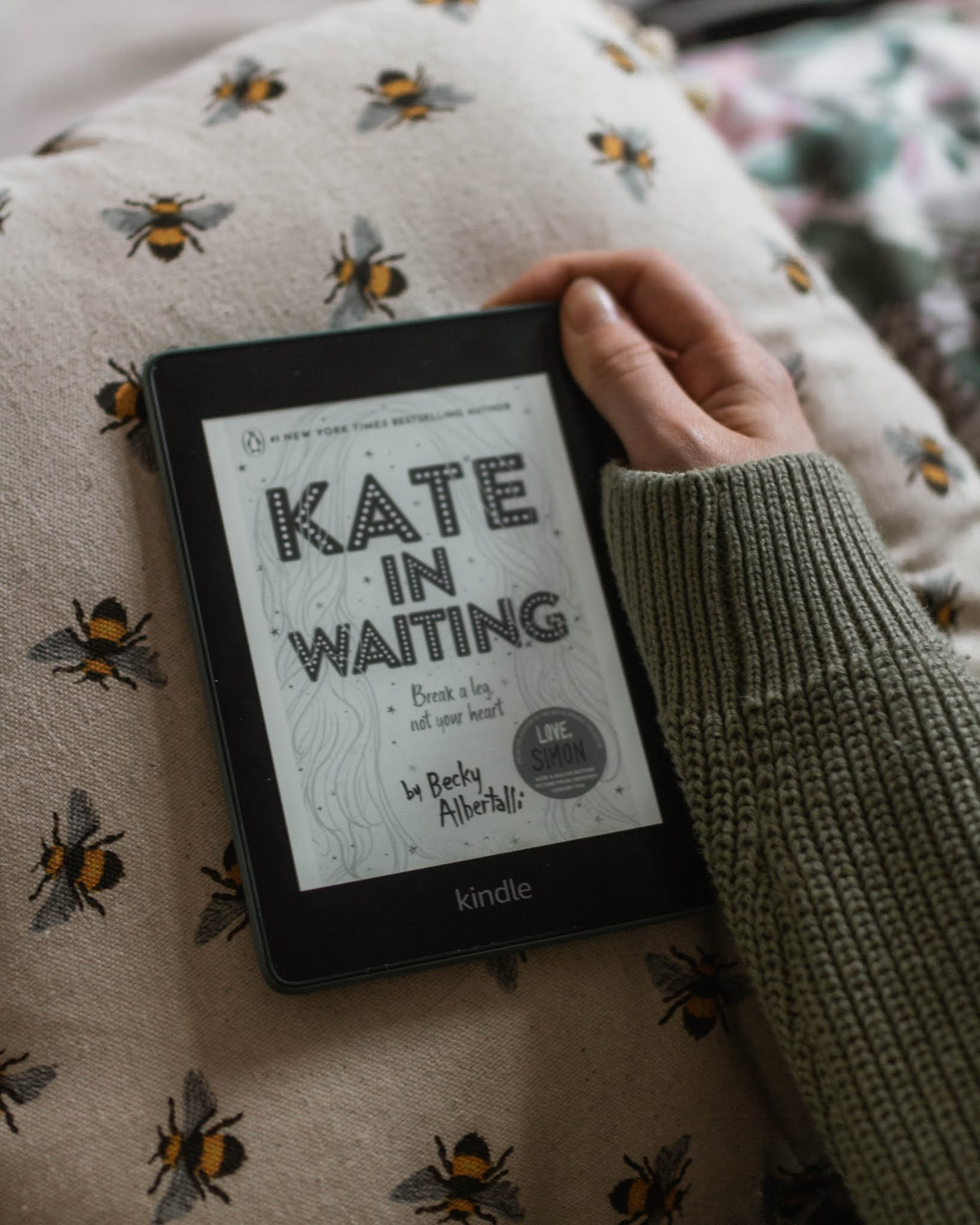 kindle paperwhite displaying kate in waiting by becky albertalli cover sitting on bee patterned cushion