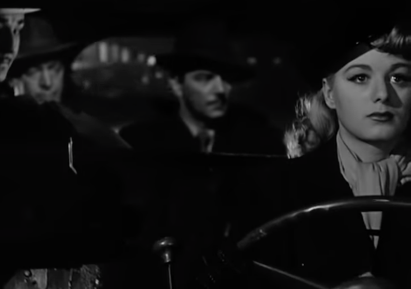 Black and white movie still of cabdriver and passengers