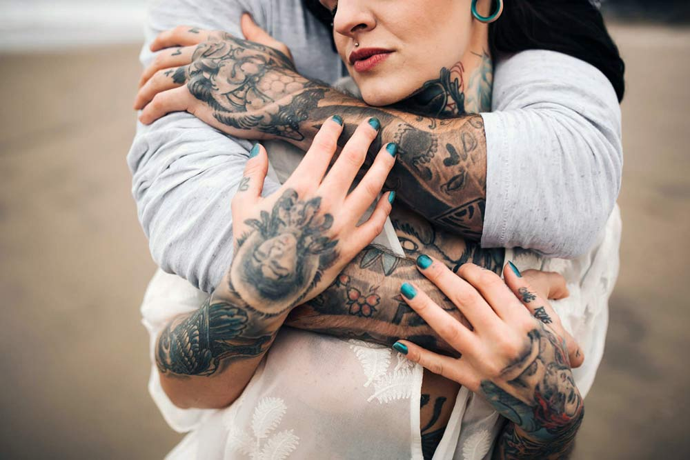 pareja tatuada dandose un abrazo