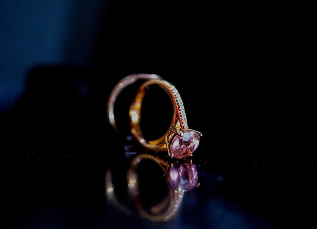 Close up of a gold ring with a pink gemstone.