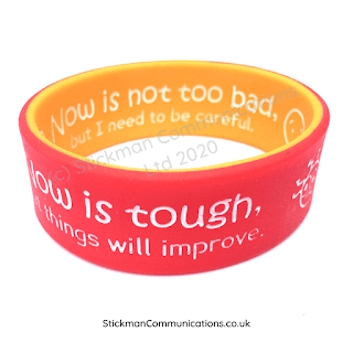 """2cm wide silicone wristband. Red outside with text """"Now is tough, but things will improve."""" Inside orange with text """"Now is not too bad, but I need to be careful""""."""