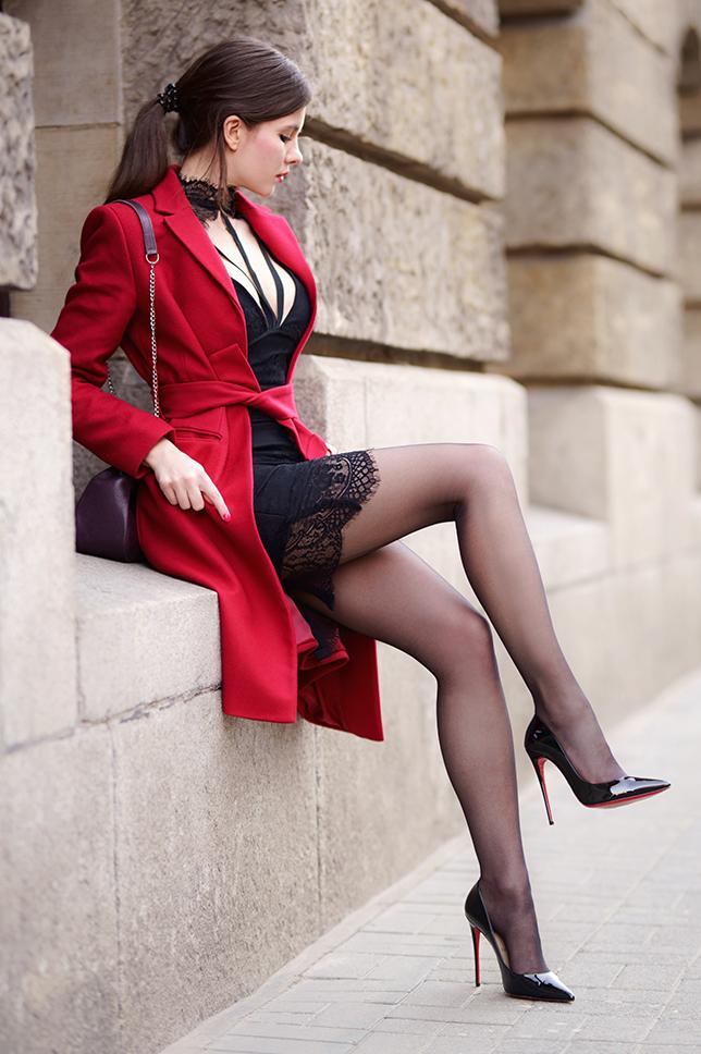 Czerwony wełniany płaszcz, czarna koronkowa sukienka i szpilki z czerwoną podeszwą