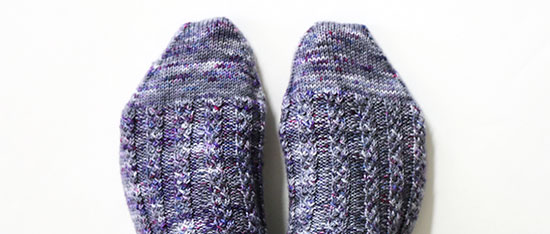 Toes of feet wearing hand knit wool socks in shades of gray with spots of purple against a white background.