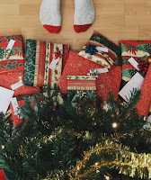Christmas gifts under a tree, with feet.
