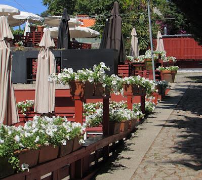 Vasos de flores brancas, guarda-sóis fechados e mesas e cadeiras