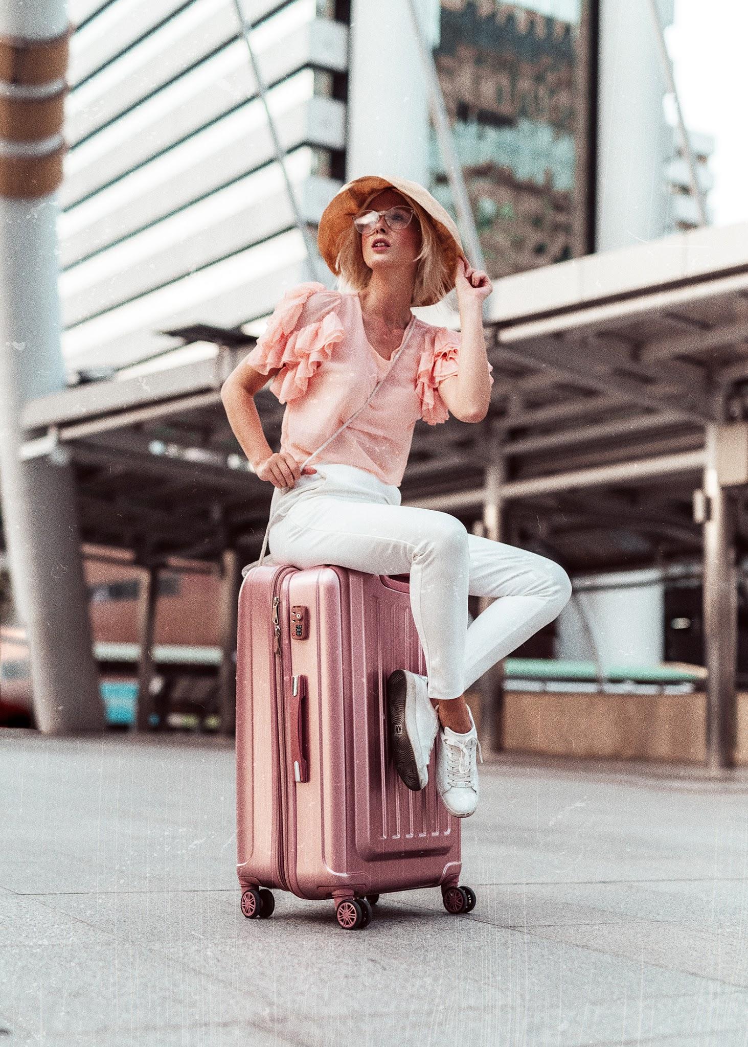 Elegant woman sitting on suitcase photography