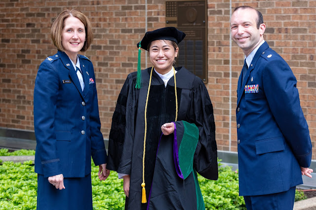 Clara Hua, pictured center in cap and gown, a person on either side of her