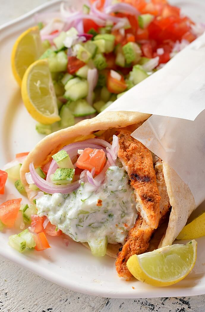a white plate with easy chicken gyro with salad and homemade tzatziki