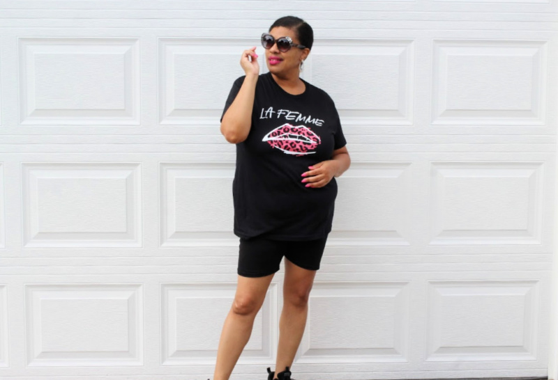 a woman wearing a black tshirt with pink leopard lips on it