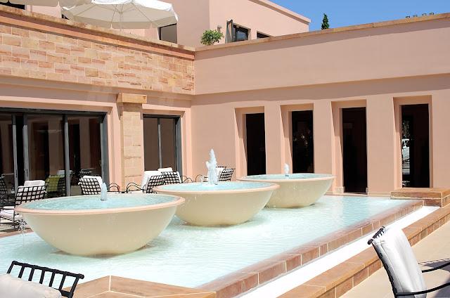 חצר מלון בו יש מזרקה עם שלוש קערות מהן בוקעים המים