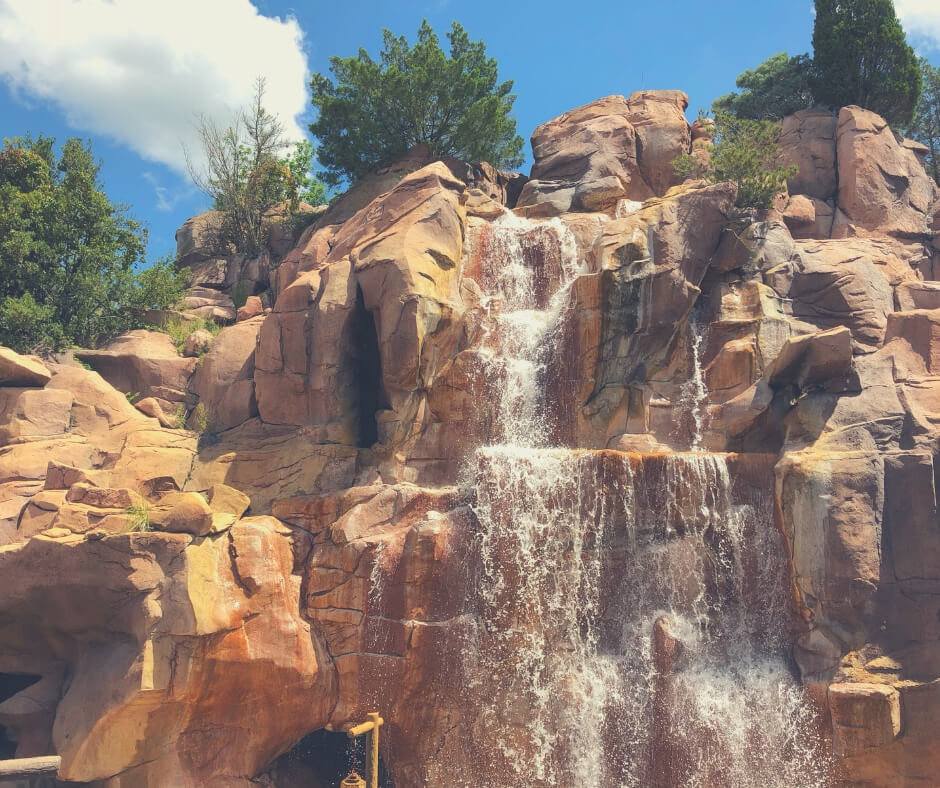 17 Must Dos For Your First Visit To Walt Disney World | Visit the Canada Pavilion and you'll see this beautiful waterfall spilling over the gorgeous orange rocks.