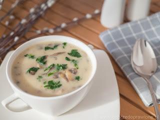 Zupa pieczarkowa w białej bulionówce na drewnianym stoliku