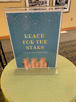 """Reach for the Stars"" sign with image of hands reaching up toward the stars in the sky"