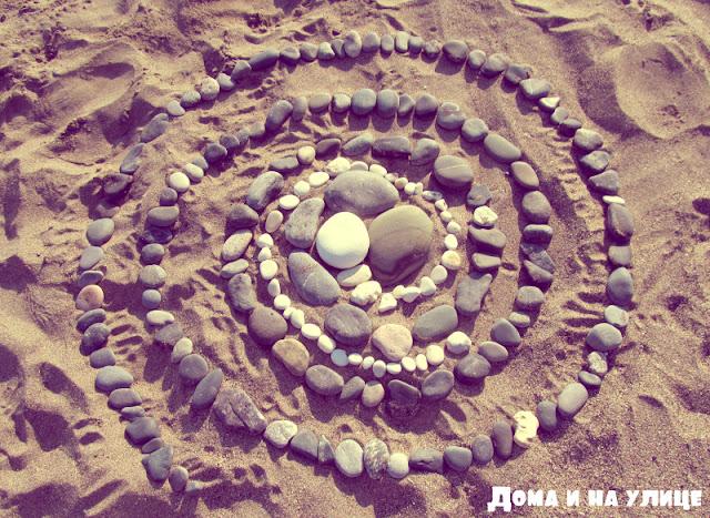 Спираль из камней игры на галечном пляже