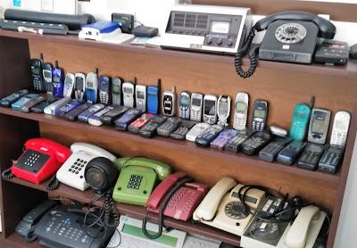 Fotografia de uma prateleira, na sala do curso de atendimento telefónico, com uma enorme quantidade de modelos antigos de telefones