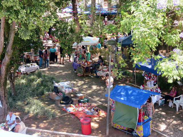 Some of the street market tents by the shadow of the trees.