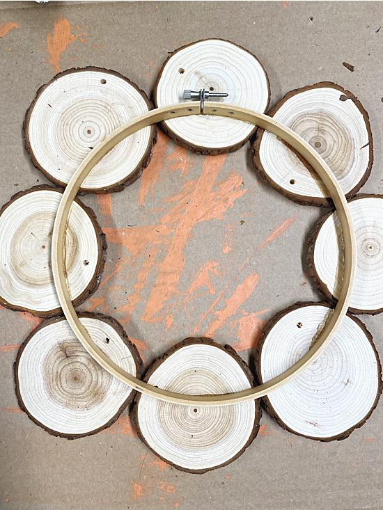 wood slices being glued to embroidery hoop