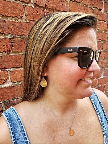 A woman in sunglasses and leather earrings with a brick wall background