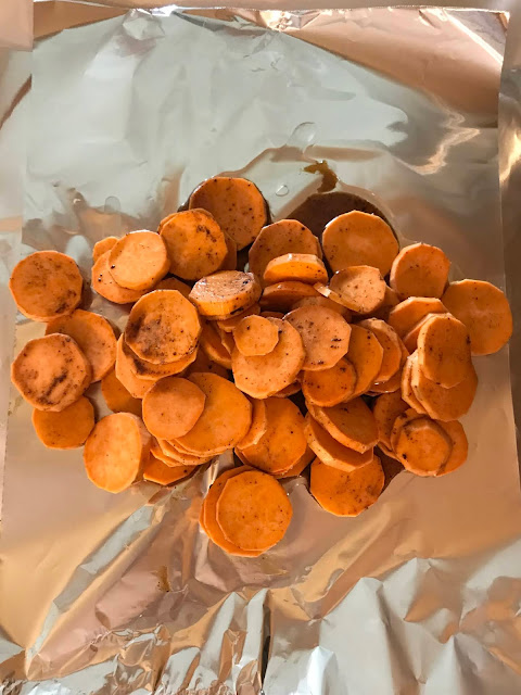 Raw sweet potatoes being placed onto the foil.