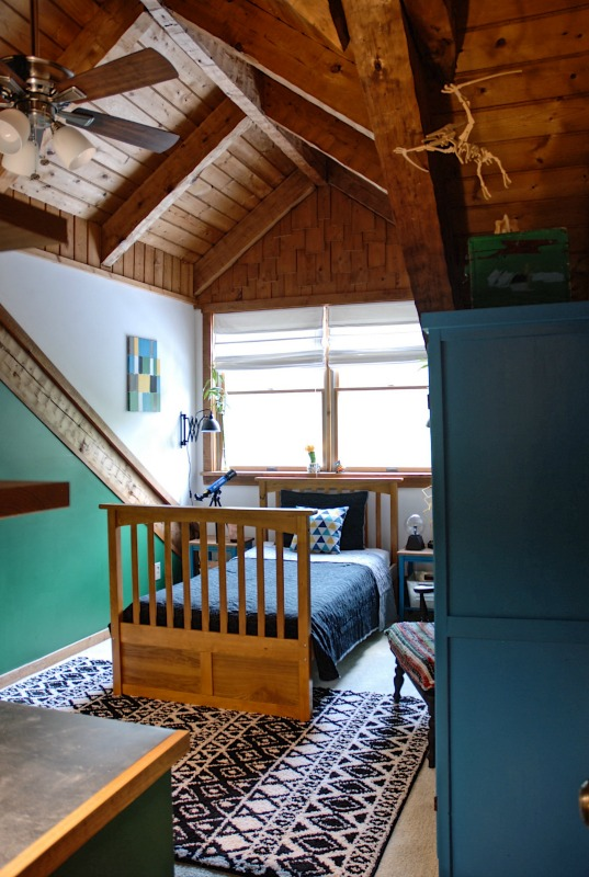 A colorful science and dinosaur themed boy's room in a log cabin home, featuring a built in desk with DIY stainless steel counter top and built in shelves. Paint colors are Cat Eye Green and Ocean Soul Blue.
