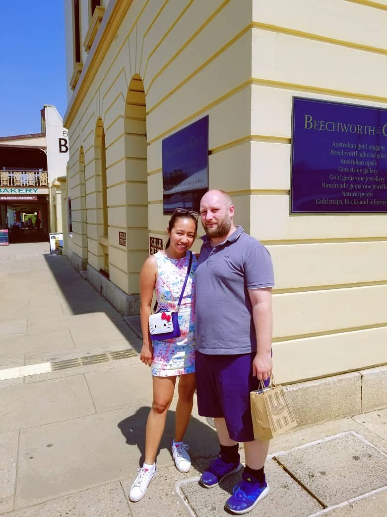 A picture with a man and a woman, with an old building in the background.