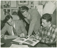 A black and white photograph of three men crowded around a table and examining a book of photographs.