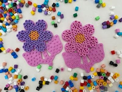 Hama bead flower designs on pegboard