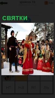 На снегу около дома люди в костюмах отмечают святки, танцуют и поют