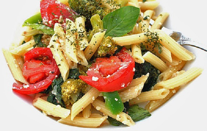 this is a penne pasta with vegetables in a white bowl with tomatoes and broccoli