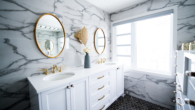 Bathroom double vanity with white cabinets and sinks with gold fixtures.