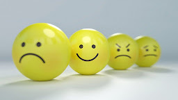 a group of four balls with sad and angry faces, but one stands out in a pleasing way with a happy face