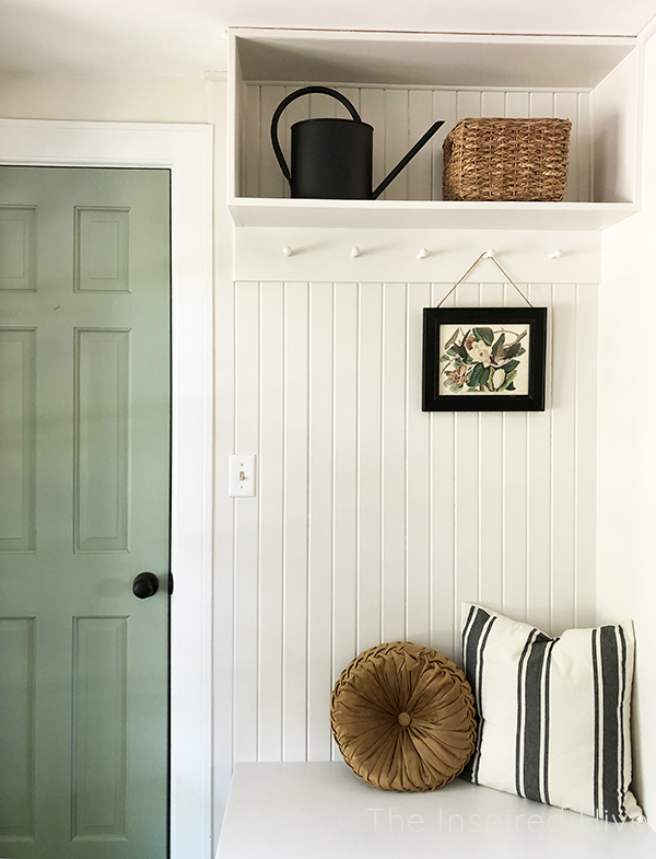 Farmhouse mudroom with tongue and groove, peg rail, and green painted door.