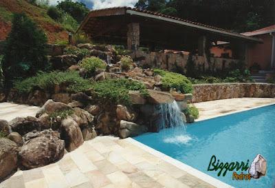 Cascata de pedra na piscina, com pedra moledo, tipo pedra natural. Piscina com o piso de pedra São Tomé e com o muro de pedra moledo.