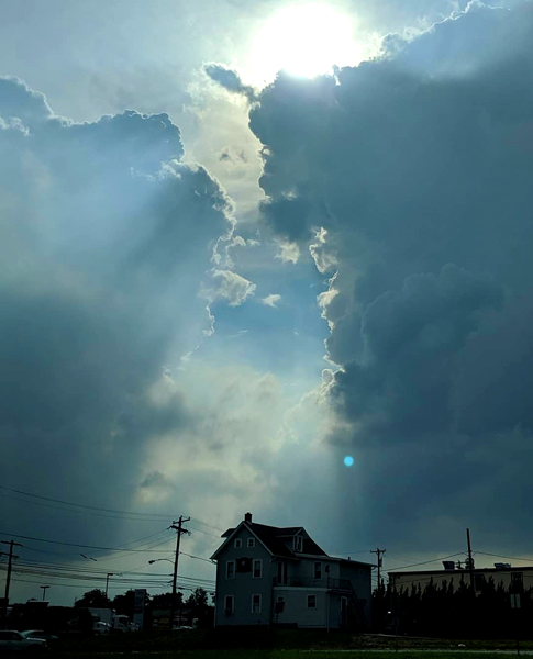 image of a cloudy blue sky with the clouds just breaking apart to allow sun to stream between them, just above a house in the distance