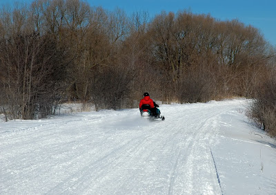 A snowmobile with it's rider along a snow-covered trail.