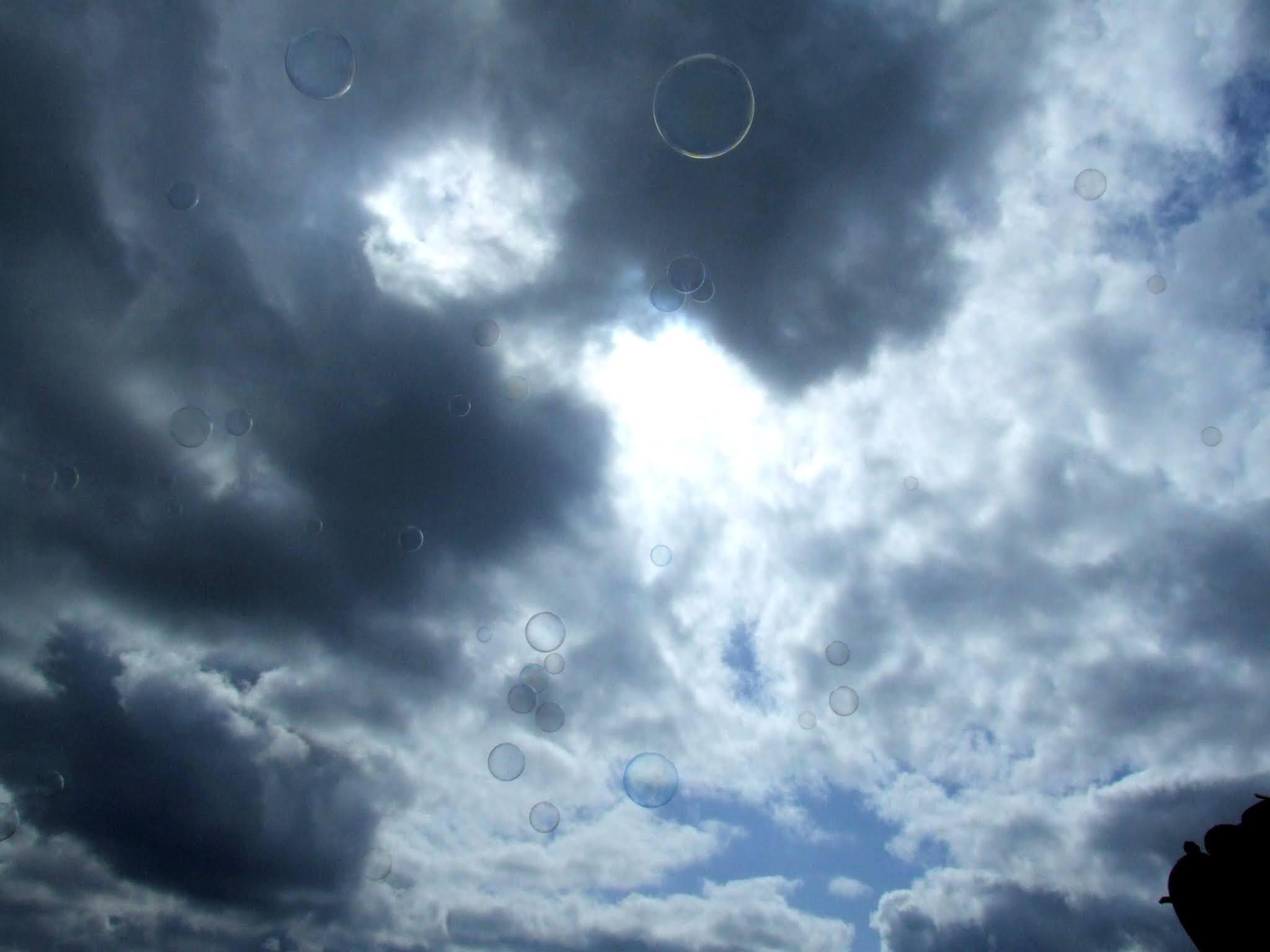 真っ青な空と白い雲に、シャボン玉が飛んでいる風景の写真素材です。どこかファンタジックで非日常な印象を与えます。