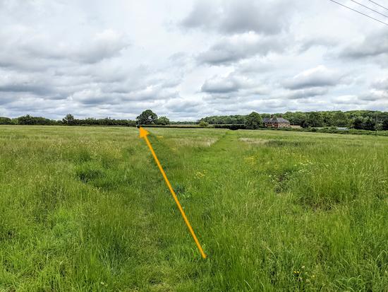 Follow the path diagonally NE across the field