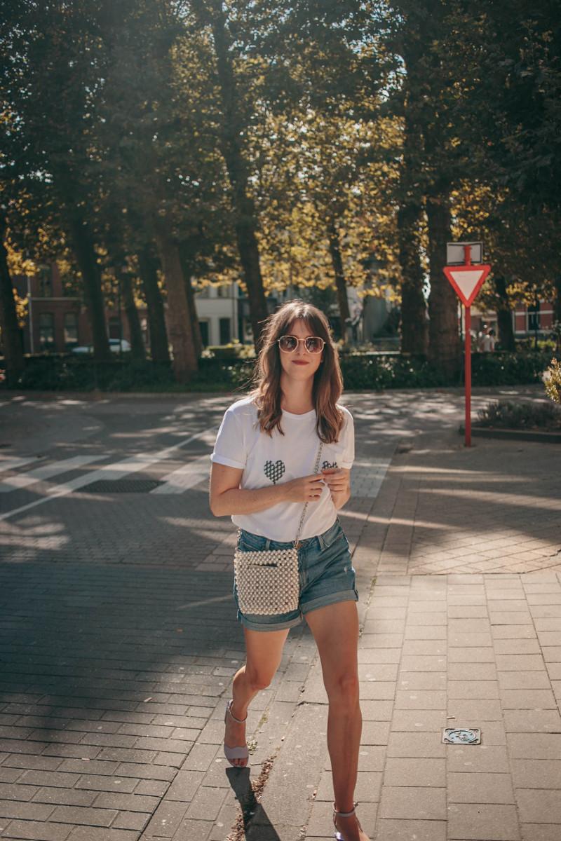 denim shorts, pearl handbag and white tee