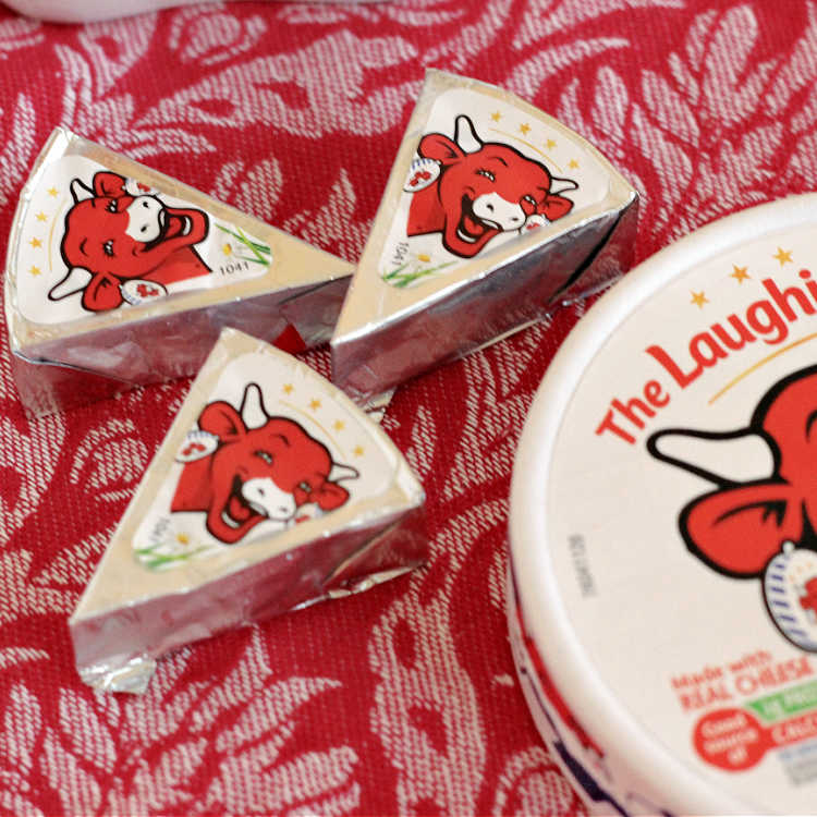 Laughing Cow Cheese Wedges on a red background
