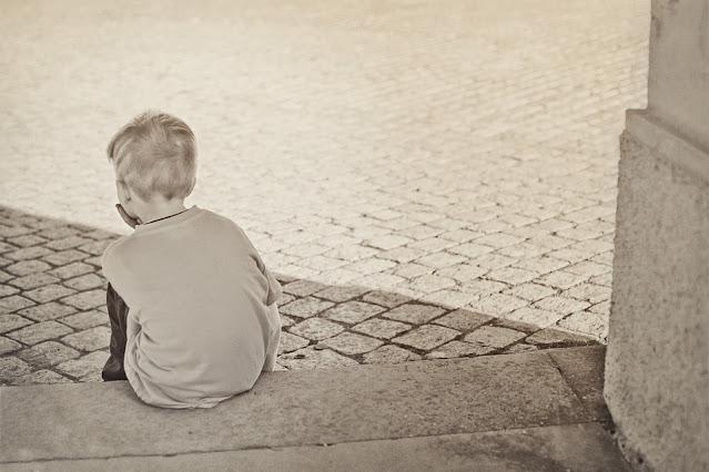 طفل يجلس على الرصيف ويفكر