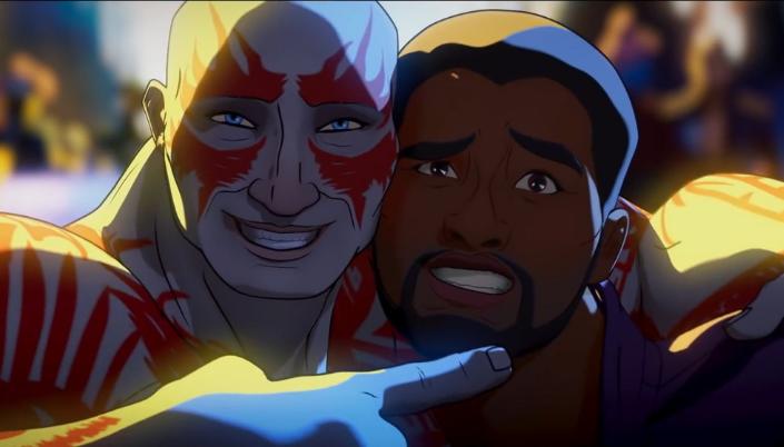 Imagem: cena do episódio com o Drax, um homem humanóide careca e cinzento com marcas vermelhas por todo o seu corpo e ao redor dos olhos azuis, sorrindo e abraçando o Senhor das Estrelas, um homem negro com um casaco roxo com detalhes alaranjados.