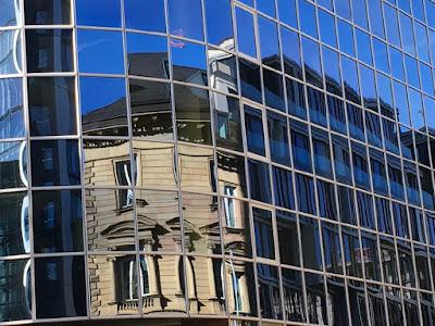 Eine alte Fassade spiegelt sich in einer modernen Glasfassade