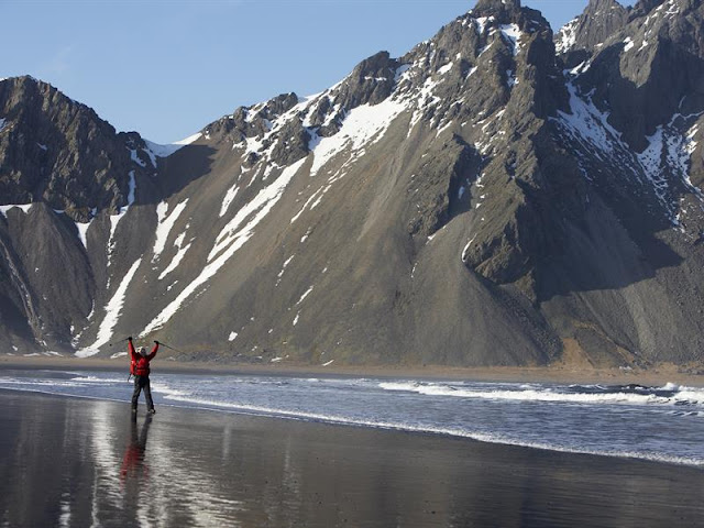 iceland mountain range with man in water below