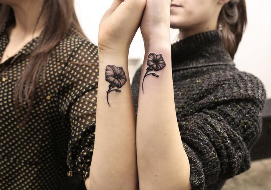 Tatuaje dos flores en anterbrazo de dos chicas cogidas de la amano