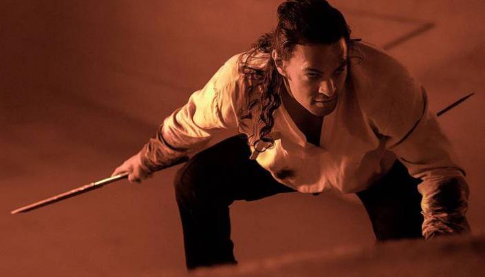 Imagem: o personagem Duncan Idaho, intepretado por Jason Momoa, um homem com uma espada, agachado e observando alguém em sua frente, uma camisa branca e calças escuras, os cabelos longos amarrados no topo da cabeça, em uma sala de iluminação alaranjada.
