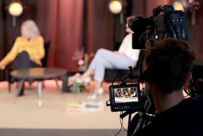 TV-fotograf filmar gäster i TV-soffor i suddig bakgrund.