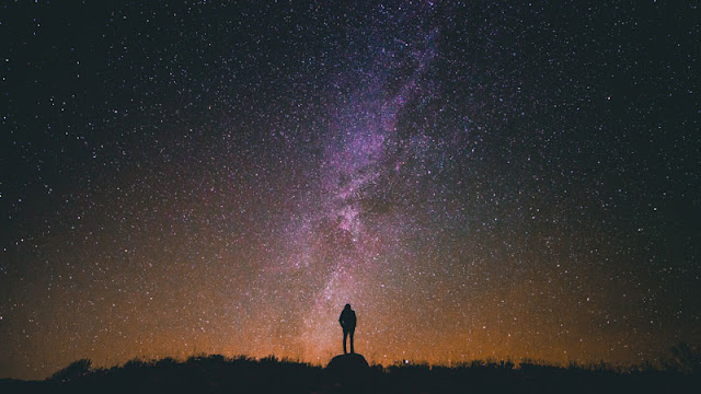 Man standing beneath starry sky